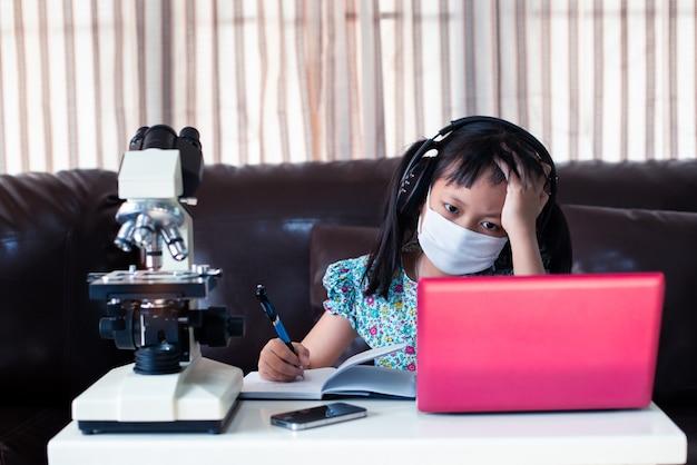 Menina criança estresse usando máscara facial e fones de ouvido aprendendo on-line usando laptop e microscópio em casa, educação a distância Foto Premium