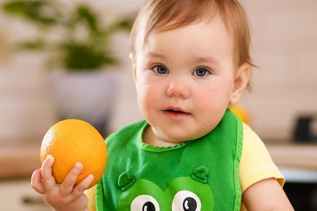 Menina criança feliz na cozinha come frutas saborosas, laranjas doces. Foto Premium