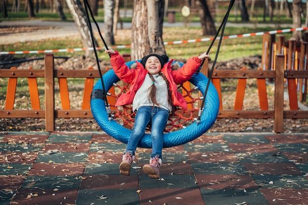 Menina criança feliz no balanço. criança brincando no pacote de outono. Foto gratuita