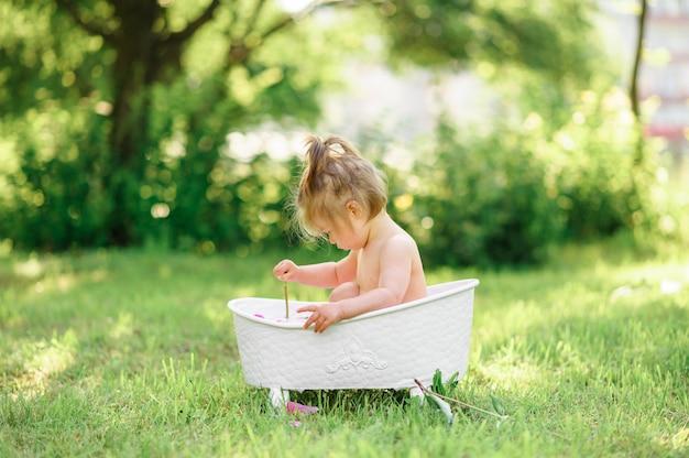 Menina criança feliz toma um banho de leite com pétalas. menina em um banho de leite em um verde. buquês de peônias rosa. banho de bebê. higiene e cuidados para crianças pequenas. Foto Premium