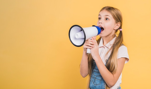 Menina, criança, gritando, através, megafone, ficar, contra, fundo amarelo Foto gratuita