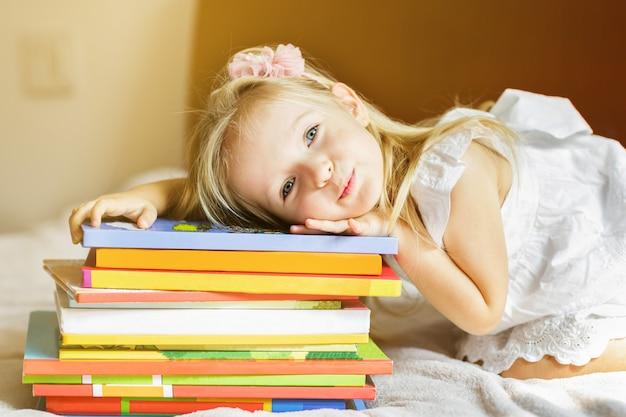 Menina, criança, mentindo, cama, com, livros Foto Premium