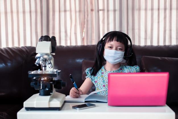 Menina criança vestindo máscara facial e fones de ouvido aprendendo on-line usando o laptop e o microscópio em casa, educação a distância Foto Premium