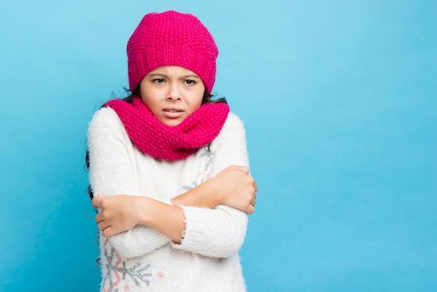 Menina cruzando os braços e sendo frio fundo azul Foto gratuita