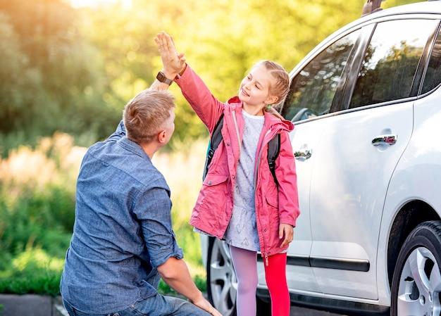 Menina cumprimentando o pai depois da escola perto do carro Foto Premium