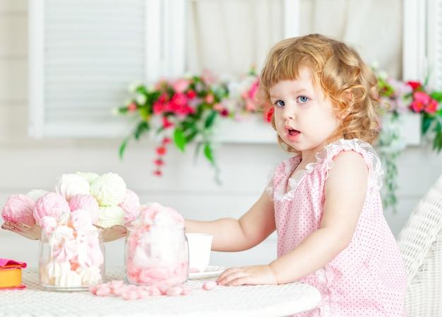 Menina curly bonito pequena em um vestido cor-de-rosa com laço e às bolinhas que sentam-se na tabela e que comem doces diferentes. Foto Premium