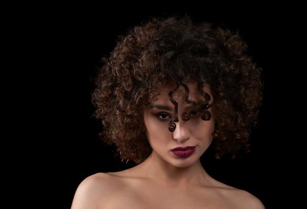 Menina curly exótica que olha a câmera e o levantamento. Foto Premium