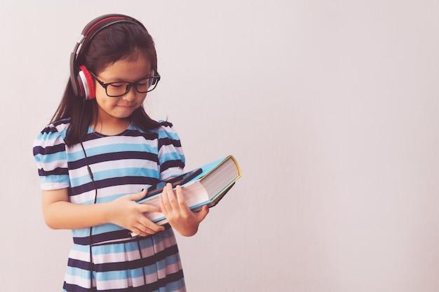 Menina da ásia com fones de ouvido, ouvindo música e segurando livros Foto Premium