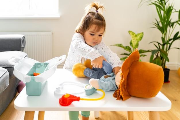 Menina da criança bebê brincando com brinquedos e kit médico boneca Foto Premium