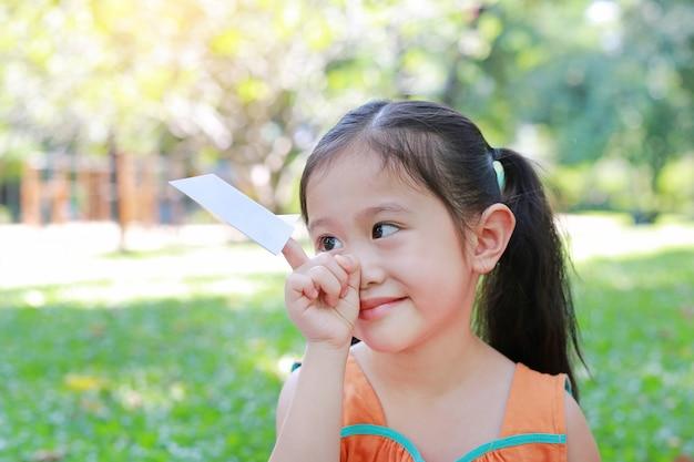 Menina da criança pequena que mostra um foguete do livro