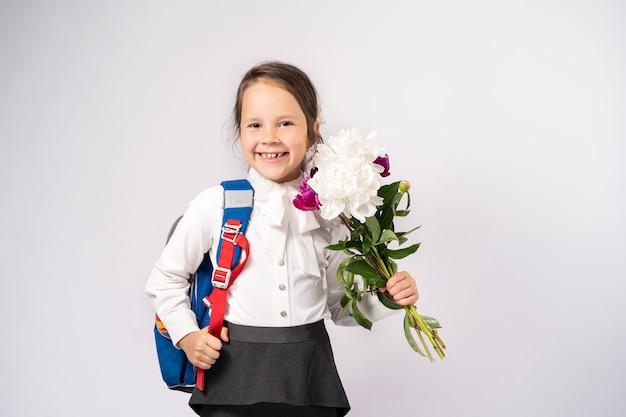 Menina da escola de primeiro grau em uma camisa branca segurando flores e uma mochila Foto Premium