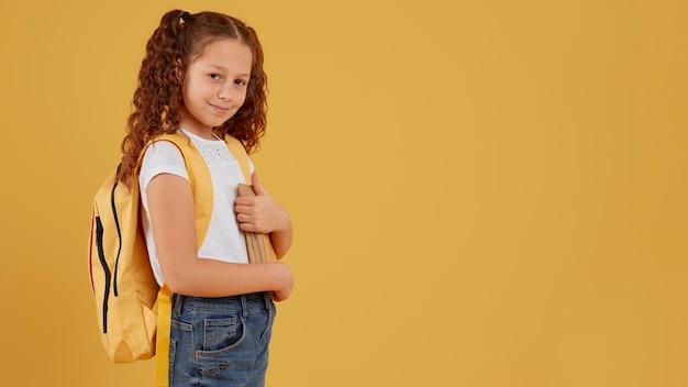 Menina da escola em pé, vista lateral, cópia espaço Foto gratuita