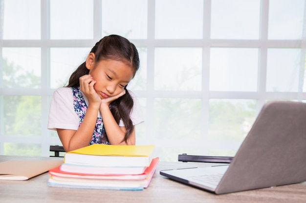 Menina da escola primária se sentir chato de estudar Foto Premium