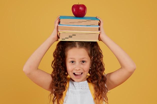 Menina da escola segurando livros e maçã na cabeça Foto gratuita