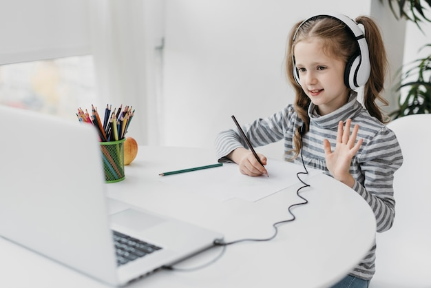 Menina da escola usando fones de ouvido escola virtual Foto gratuita