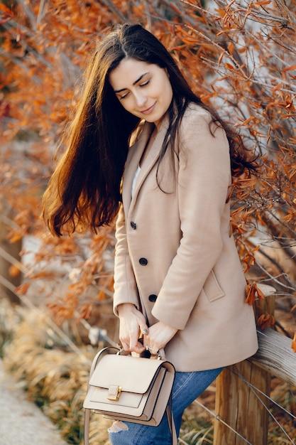 Menina da moda andando em um parque sspring Foto gratuita