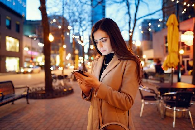 Menina da moda andando em uma cidade de noite Foto gratuita