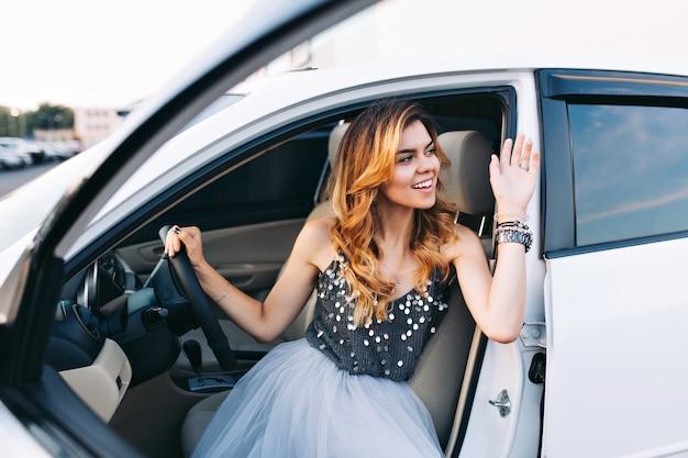 Menina da moda em saia de tule, dirigindo um carro branco. ela está agradecendo alguém ao lado. Foto gratuita