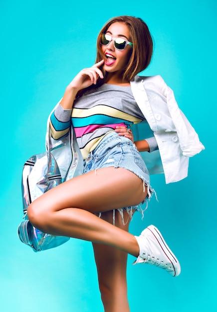 Menina da moda posando no estúdio, vestindo roupa esportiva casual inteligente, estilo empresarial, tons pastel doces, óculos escuros, jeans de mochila e jaqueta, fundo de hortelã, mulher elegante. Foto gratuita