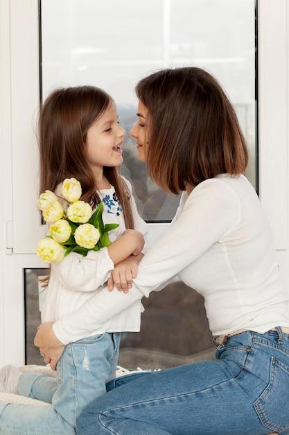 Menina dando flores para mãe Foto gratuita
