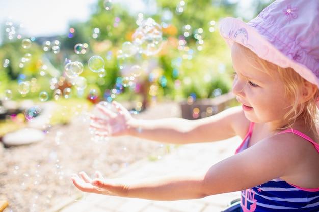 Menina de 3 anos de idade em um chapéu-de-rosa e maiô despojado azul tomando banho no quintal e brincando com bolhas. Foto Premium