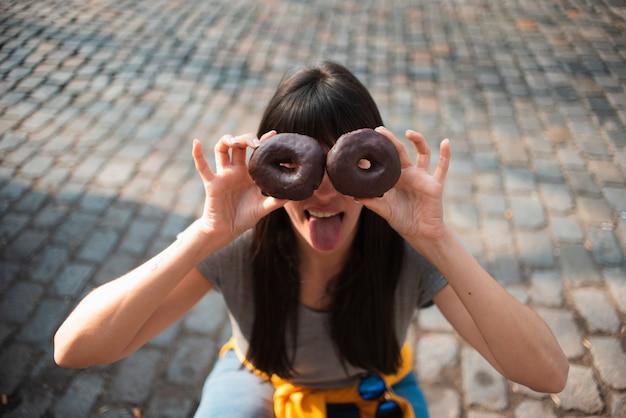 Menina de alto ângulo com donuts Foto gratuita