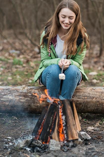 Menina de alto ângulo, cozinhar marshmallow Foto gratuita