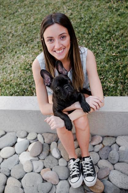 Menina de alto ângulo, segurando seu filhote de cachorro Foto gratuita