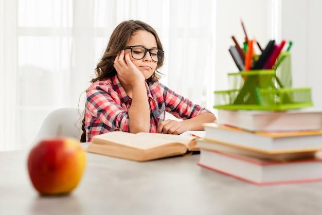 Menina de ângulo baixo com óculos estudando Foto gratuita