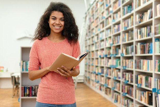 Menina de baixo ângulo na leitura da biblioteca Foto gratuita