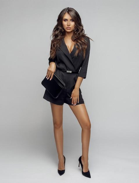 Menina de beleza no macacão preto elegante e saltos. Foto Premium