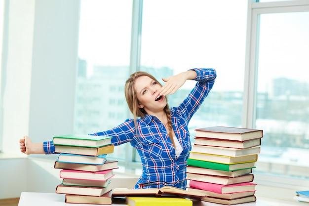 Menina de bocejo cercado por livros Foto gratuita
