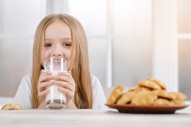 Menina de cabelo loiro bebe um copo com leite Foto Premium