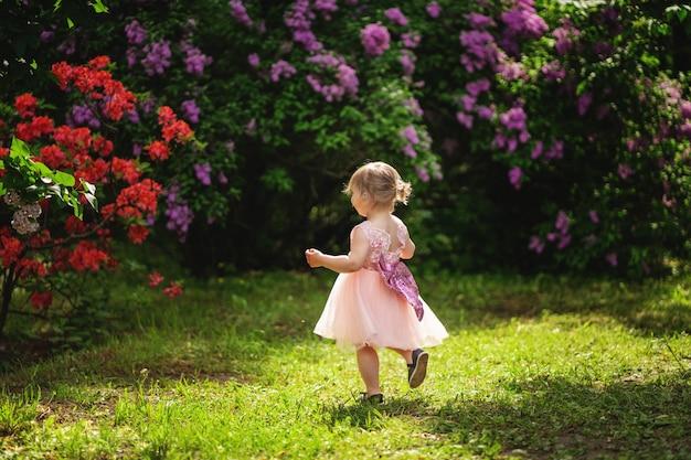 Menina de cabelos loiros em um vestido rosa é executado em um parque florido Foto Premium