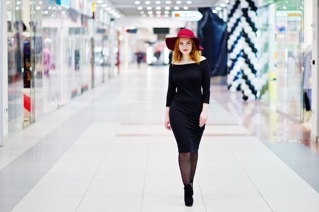Menina de cabelos vermelha moda vestir vestido preto e chapéu vermelho, colocados no comércio centro comercial. Foto Premium