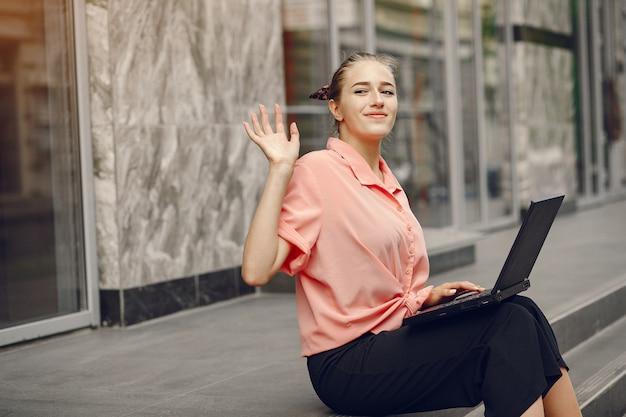 Menina de camisa rosa, sentado perto de casa e usar o laptop Foto gratuita