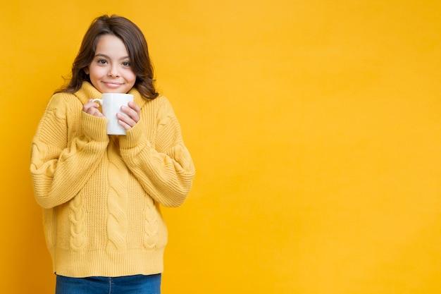Menina de camisola amarela com copo nas mãos Foto gratuita