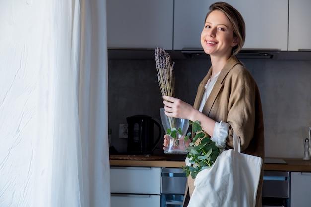 Menina de casaco com sacola e plantas em uma cozinha Foto Premium