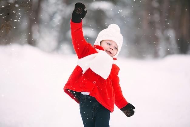 Menina de casaco vermelho com um ursinho de pelúcia se divertindo inn dia de inverno Foto Premium
