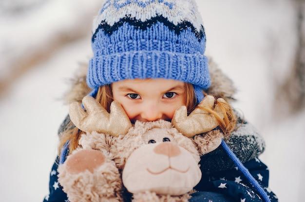 Menina de chapéu azul jogando em uma floresta de inverno Foto gratuita