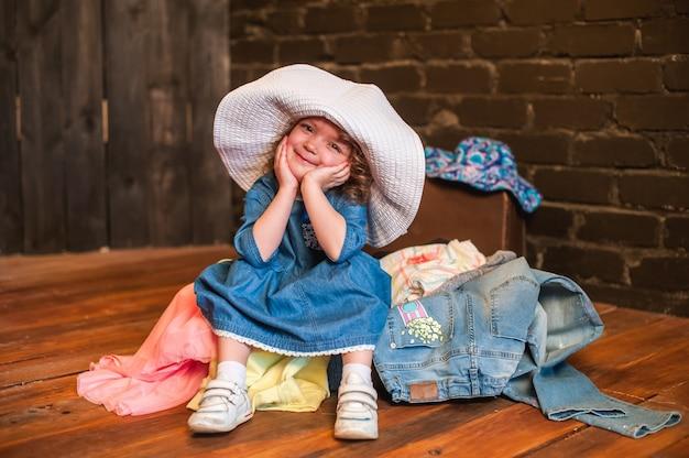 Menina de chapéu branco sentado na mala com as coisas e olhar para a câmera Foto Premium