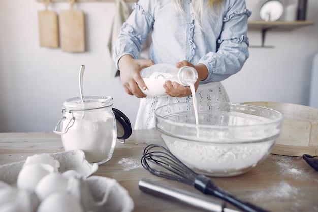 Menina de chapéu branco shef cozinhar a massa para biscoitos Foto gratuita