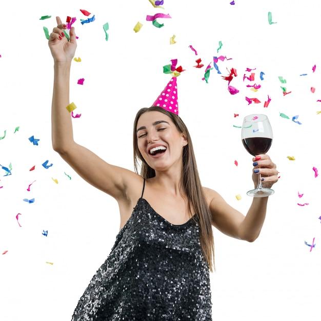 Menina de chapéu de festa com copo de vinho tinto dançando sob confete Foto Premium