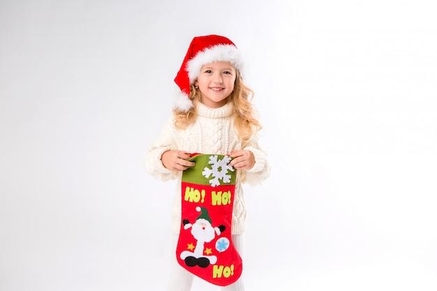 Menina de chapéu de papai noel está segurando uma meia de natal Foto Premium