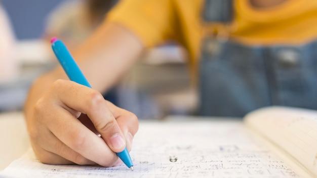 Menina de close-up escrevendo Foto gratuita