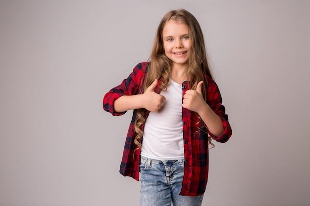 Menina de colegial com polegares para cima Foto Premium