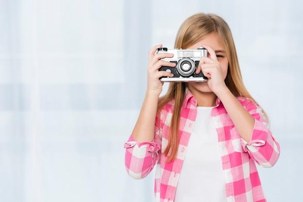 Menina de cópia-espaço tirando fotos Foto gratuita