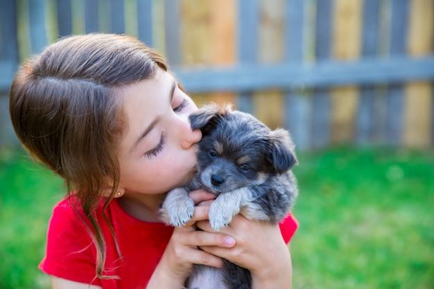 Menina de crianças beijando seu cachorrinho chihuahua doggy Foto Premium