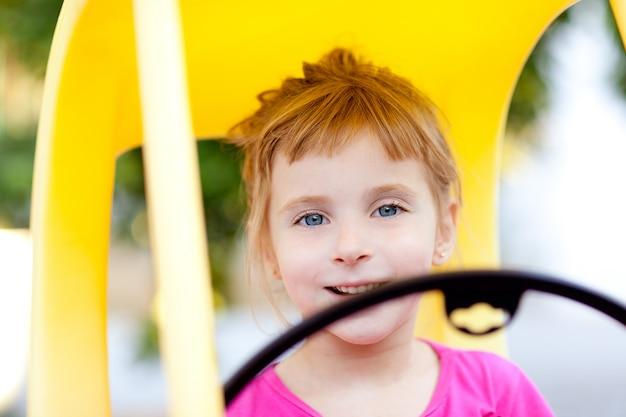 Menina de crianças loiras dirigindo carro de brinquedo Foto Premium