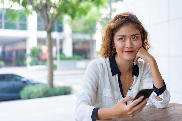 Menina de escritório asiática positiva descansando no café de rua Foto gratuita